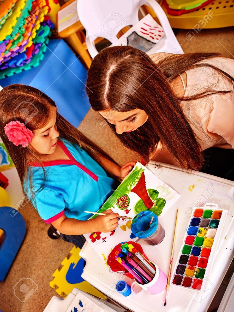 Peinture à l'enfance et à dessin dans un club pour enfants. leçon d'artisanat à l'école primaire. Kindergarten enseignant qui aide souriante ...