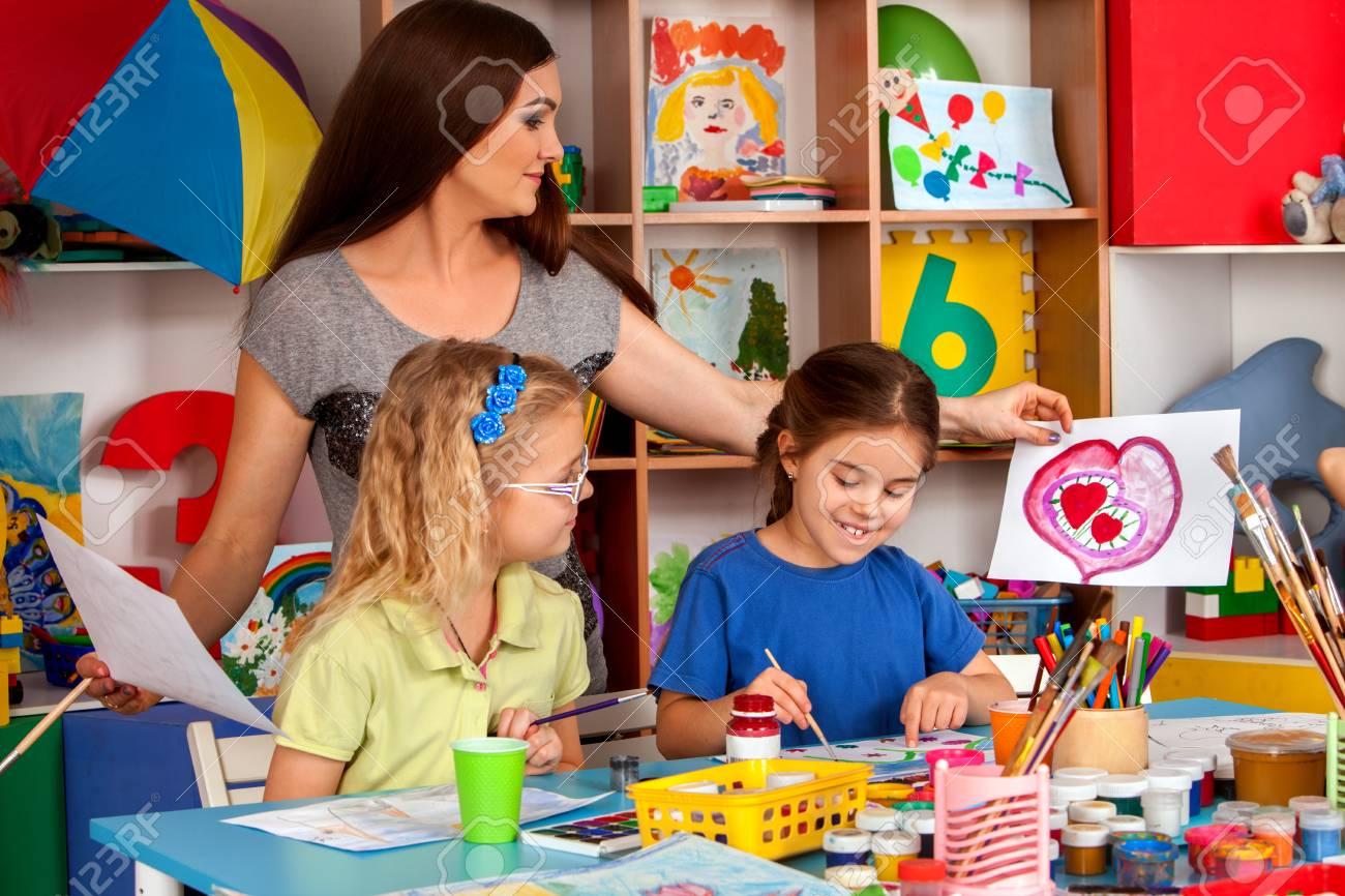 Cours d'artisanat à l'école primaire. Le professeur de maternelle et les petits étudiants travaillent ensemble. Les filles à la leçon de dessin. ...