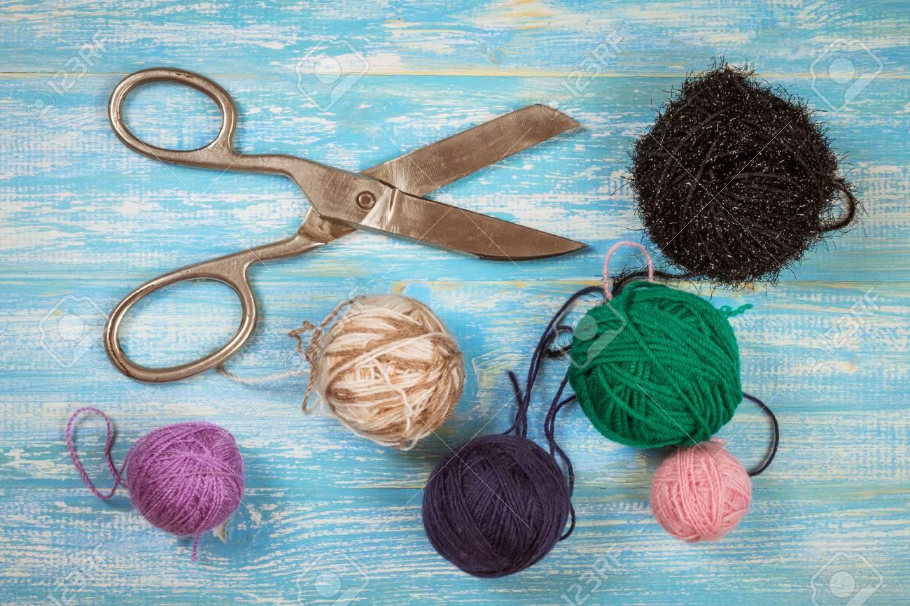 Ciseaux vintage et boules de laine sur une table en bois bleue. Le concept de l'artisanat à domicile.