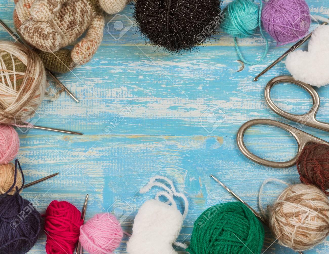 Fil multicolore avec de la laine et des ciseaux sur une table en bois. Le concept de l'artisanat à domicile.