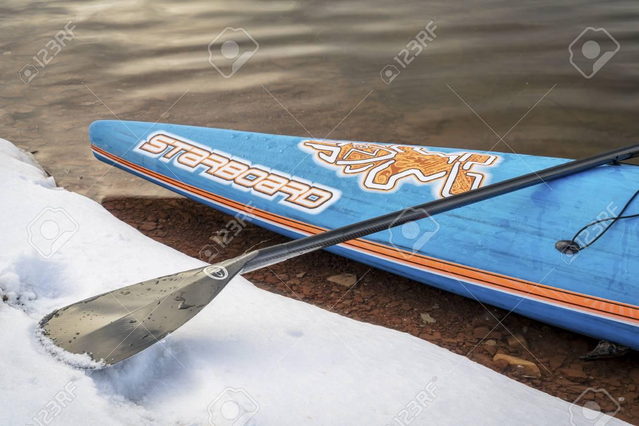 FORT COLLINS CO, É.-U. - 22 DÉCEMBRE 2016: Un arc de paddleboard de course Star Star par Starboard avec une pagaie sur la rive d'un lac dans un ...