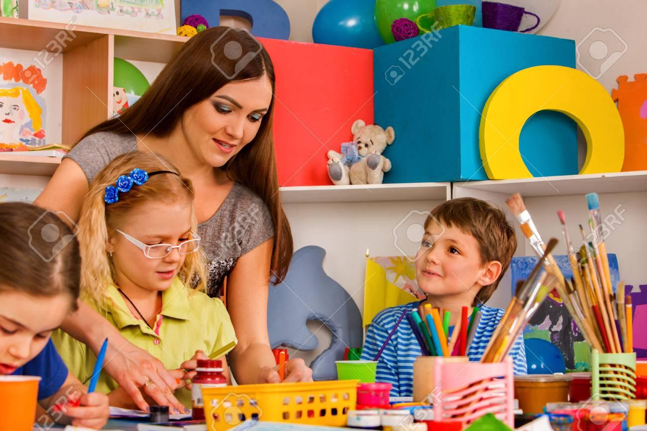 Cours d'artisanat à l'école primaire. Le professeur de maternelle et les petits étudiants travaillent ensemble. La fille et le garçon peint un stylo à ...