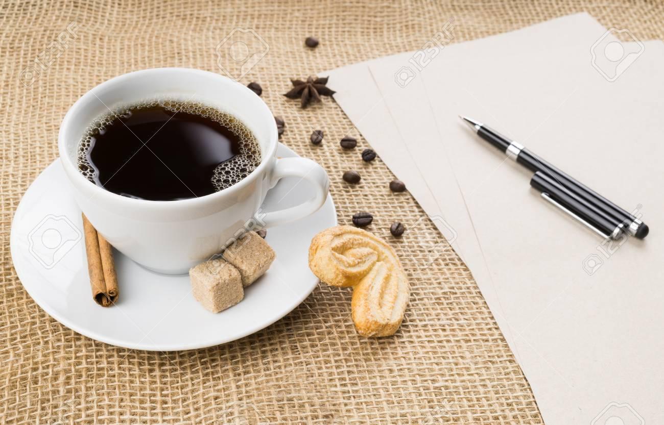 Tasse de café noir avec mousse, biscuit, cassonade, papier d'artisanat, stylo, grains de café, anis étoilé et bâton de cannelle sur fond d'un sac